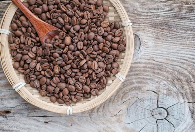 Ziarna kawy w bambusowym talerzu na drewnianej desce