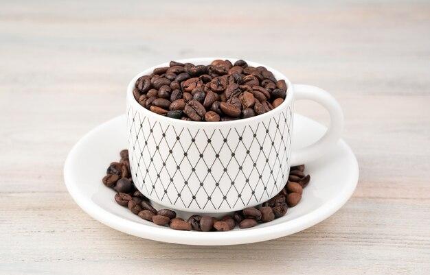 Ziarna kawy w białej ceramicznej filiżance i spodeczku na lekkim stole.