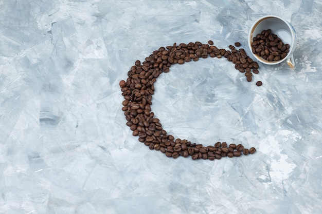 Ziarna kawy w białej filiżance na szarym tle tynku. widok z góry.