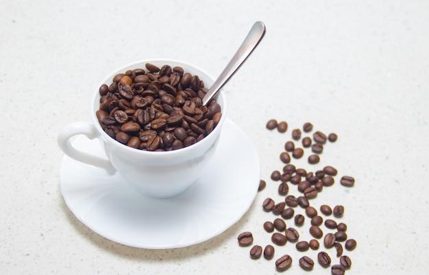Ziarna kawy w białej filiżance. przygotowanie kawy. na jasnym tle