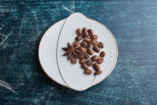 Ziarna kawy w białym ceramicznym spodku.
