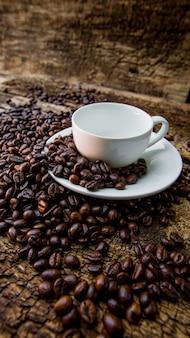 Ziarna kawy w białym kubku. kawowe fasole na drewnianym stole. ciemny stół.