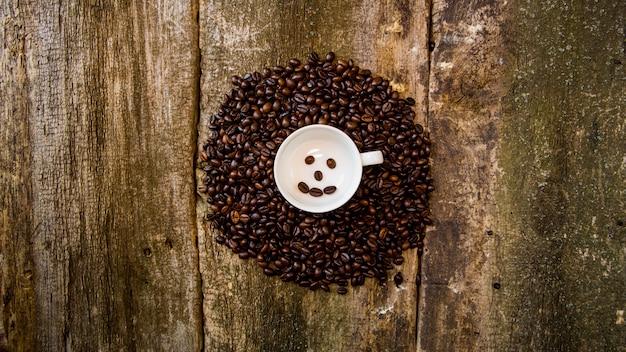 Ziarna kawy w białym kubku. kawowe fasole na drewnianym stole.