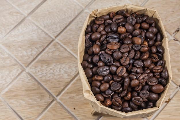 Ziarna kawy w brązowej papierowej torbie na drewnianym tle.