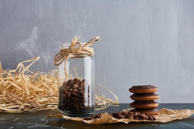 Ziarna kawy w drewnianej filiżance w szklanym słoju.