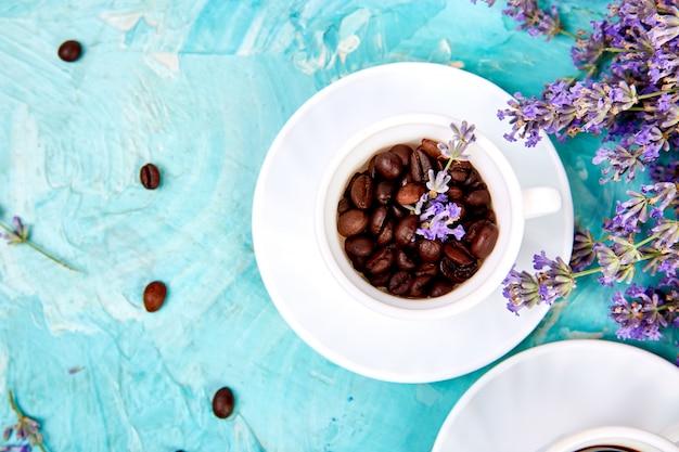 Ziarna kawy w filiżankach i kwiat lawendy na niebieskim tle z góry.