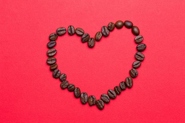 Ziarna kawy w formie serca na czerwonym tle