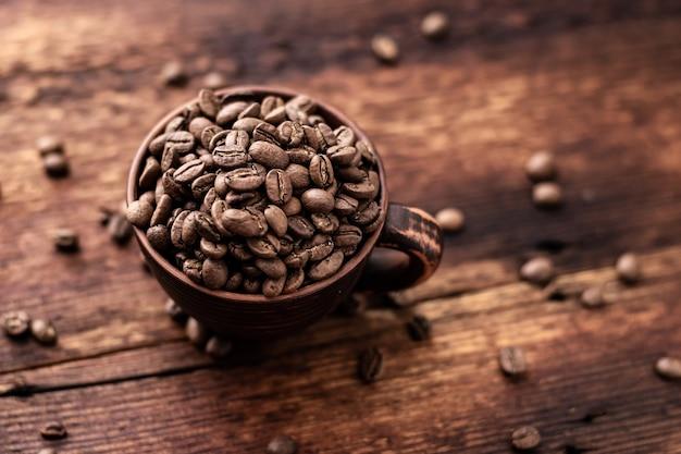 Ziarna kawy w glinianej filiżance na brązowym drewnianym starym tle.