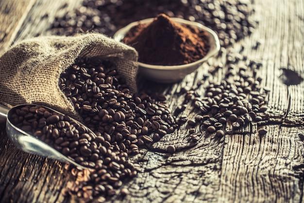 Ziarna kawy w jutowym worku na starym drewnianym stole.