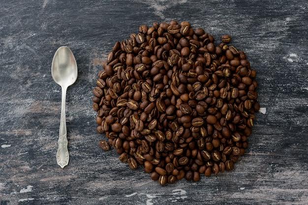 Ziarna kawy w kształcie koła, obok znajduje się srebrna łyżeczka