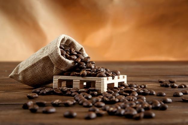 Ziarna kawy w małej torbie na drewnianym stole