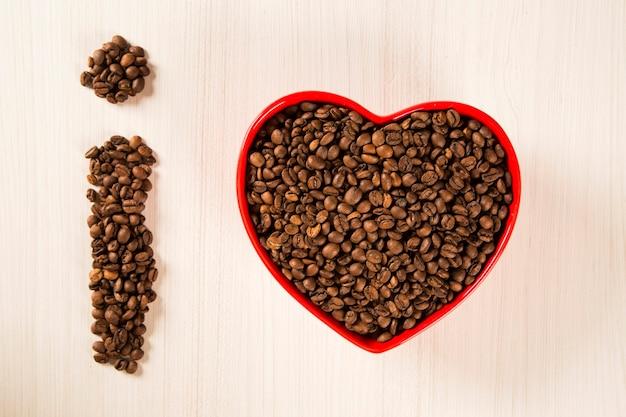 Ziarna kawy w misce serca i wykrzyknik z ziaren kawy