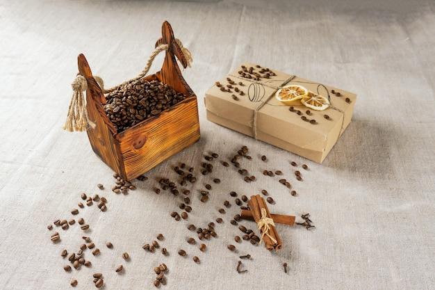 Ziarna kawy w pojemniku, cynamon, gałka muszkatołowa i goździki.