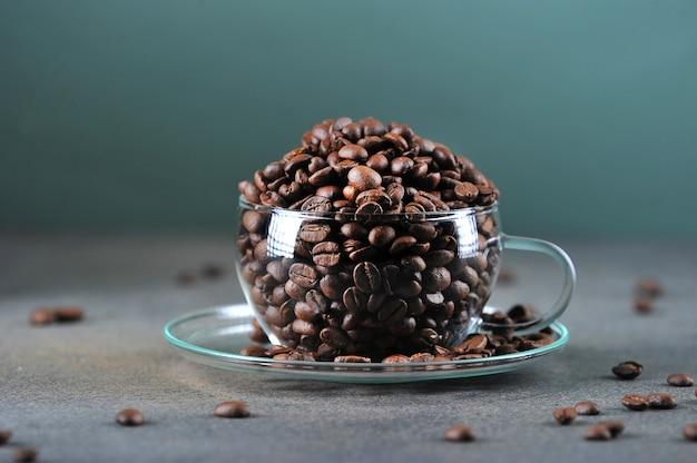 Ziarna kawy w przezroczystym szklanym kubku na szaro-zielonym kolorze