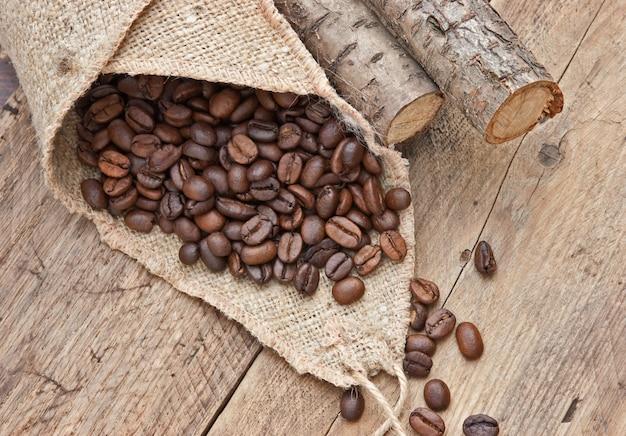 Ziarna kawy w torbie na drewnianej przestrzeni