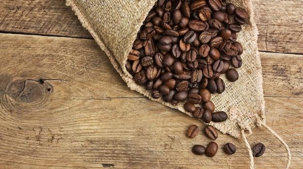 Ziarna kawy w torbie na drewnianym tle