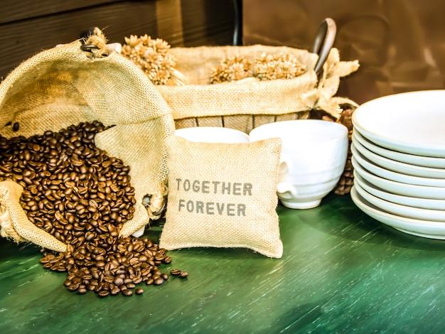 Ziarna kawy w worku są umieszczane na zielonym drewnianym stole z filiżanką kawy i białym spodkiem.