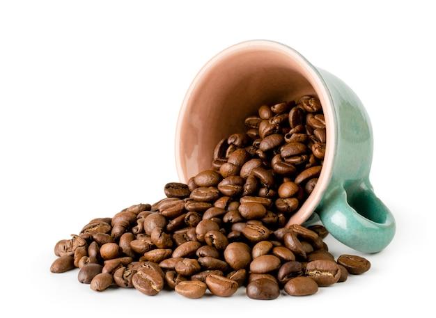 Ziarna kawy wylały się z filiżanki na białym tle