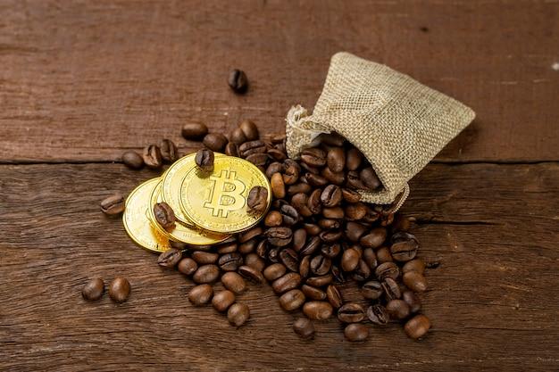 Ziarna kawy wypełnione drewnianym wiadrem, niektóre rozłożone są na stole i w torbie z tkaniny. udekoruj złotymi monetami.