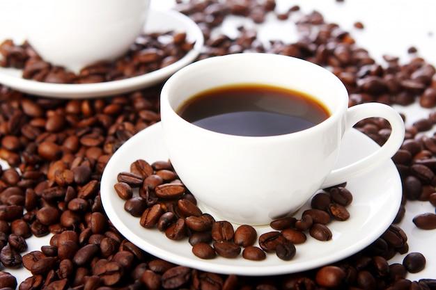 Ziarna kawy z białymi filiżankami