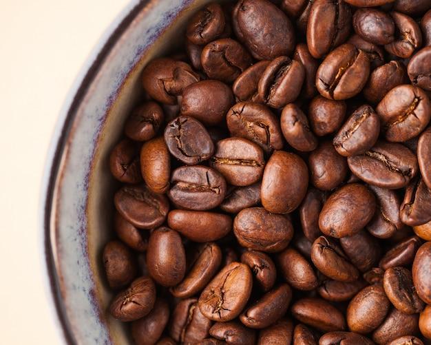 Ziarna kawy z bliska na jasnobrązowym tle. dla wygaszaczy ekranu, palarni i sprzedawców kawy.