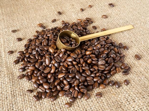 Ziarna kawy ze złotą miarką na lnianym tle tekstury