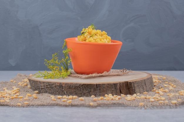 Ziarna kukurydzy w pomarańczowej misce na drewnianym talerzu.