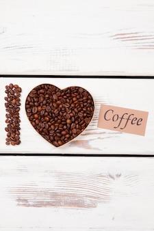 Ziarna palonej kawy w kształcie serca. kocham kawę. powierzchnia białego drewna.