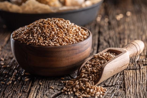 Ziarna pszenicy – główny składnik chleba wypełnionego drewnianą miseczką i drewnianą rustykalną łyżką. w tle upiecz chrupiący chleb.