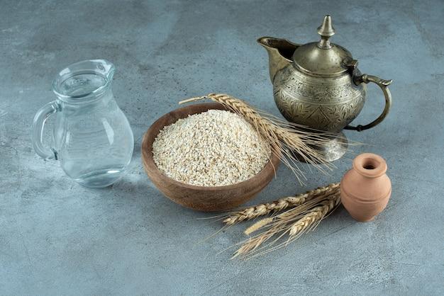 Ziarna pszenicy lub ryżu w drewnianym kubku na niebieskim tle. zdjęcie wysokiej jakości