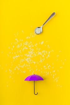 Ziarna ryżu leje od łyżki na purpurowy parasol zabawkę na żółtym stole. artystyczna koncepcja wiosennego deszczu