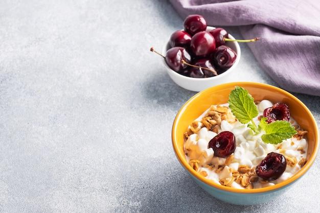 Ziarna twarogu musli ze świeżych wiśni na talerzu. koncepcja zdrowe śniadanie z twarogiem i jagodami.
