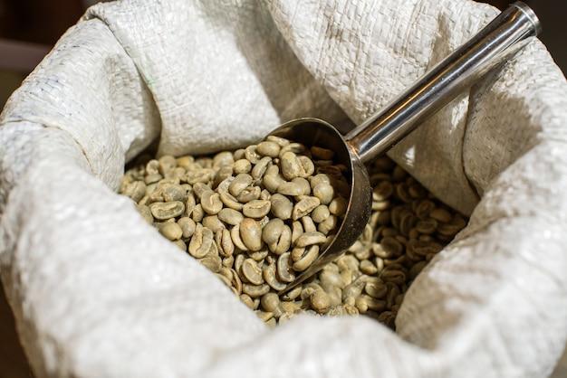 Ziarna zielonej kawy w torebce w przytulnej kawiarni