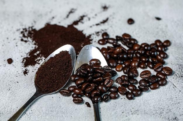 Ziarno kawy i mielona kawa na łyżce nakładają je na kamienny podkład, dobre surowce do robienia świeżej kawy
