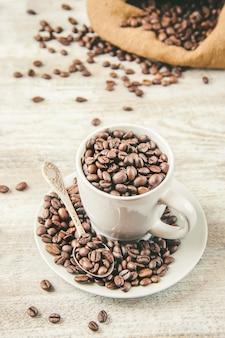 Ziarno kawy. kubek kawy. selektywne skupienie.