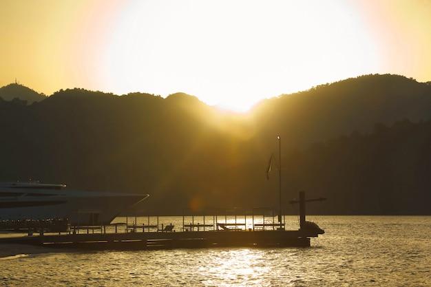 Ziarno szumu artystycznego. zachód słońca w lagunie lazurowego morza egejskiego z bujnymi górami, puszystymi chmurami, jachtem, letnia pogoda. krajobraz przyrody we wschodniej turcji. pojęcie wakacji, rekreacji i podróży