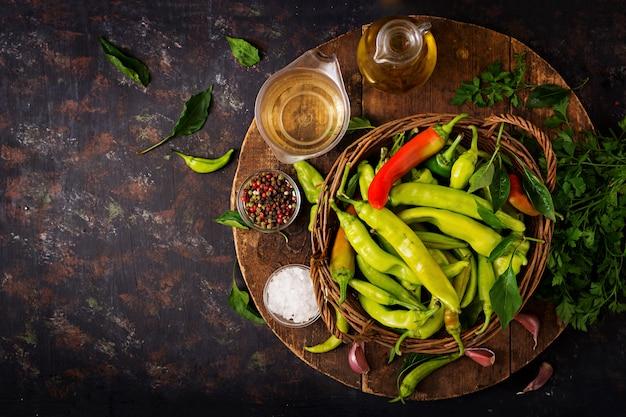 Zieleni chili pieprze w koszu na ciemnym stole