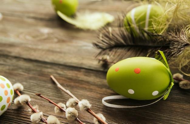 Zieleni easter jajka na starej drewnianej stół kopii przestrzeni. malowane jajka i ptasie pióra