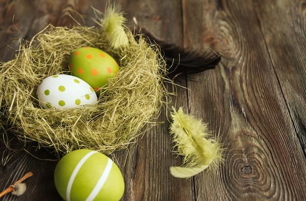 Zieleni easter jajka w sizalu gniazdują na drewnianej powierzchni kopii przestrzeni. jajka malowane