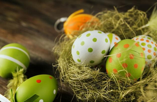 Zieleni i pomarańczowi easter jajka w sizalu gniazdują na drewnianej powierzchni kopii przestrzeni. jajka malowane