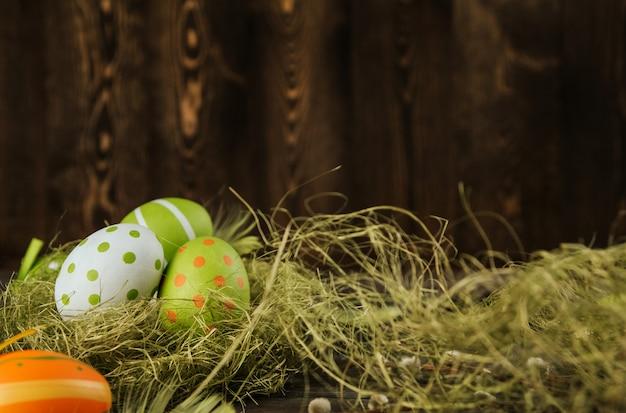 Zieleni i pomarańczowi easter jajka w sizalu gniazdują na drewnianej tło kopii przestrzeni. jajka malowane