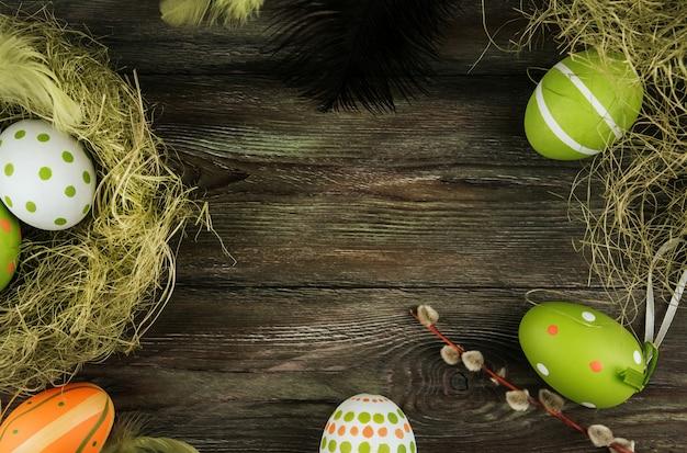 Zieleni i pomarańczowi wielkanocni jajka w sizalu gniazdują na starym drewnianym tle. ptasie pióra jajka malowane
