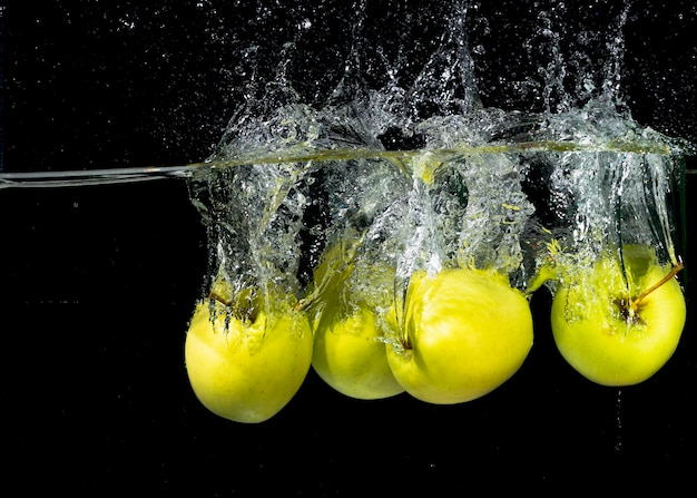 Zieleni jabłka bryzga w wodę przeciw czarnemu tłu