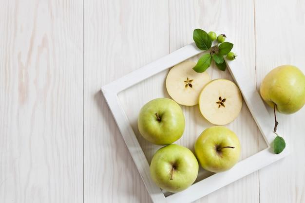 Zieleni jabłka w biel ramie na białym drewnianym tle.