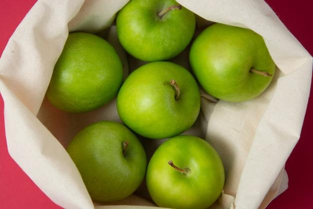 Zieleni jabłka w dużego ciężaru torbie nad czerwonym tłem. zero odpadów koncepcja.