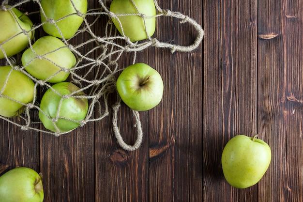Zieleni jabłka w netto torbie i wokoło odgórnego widoku na drewnianym tle