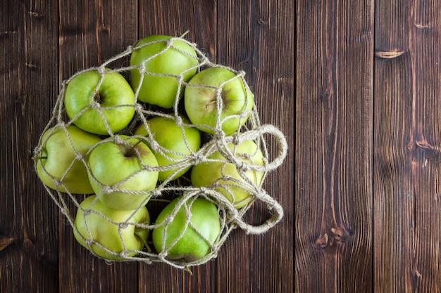 Zieleni jabłka w siatkowej torby widoku z góry na drewnianego tła bezpłatnej przestrzeni dla twój teksta