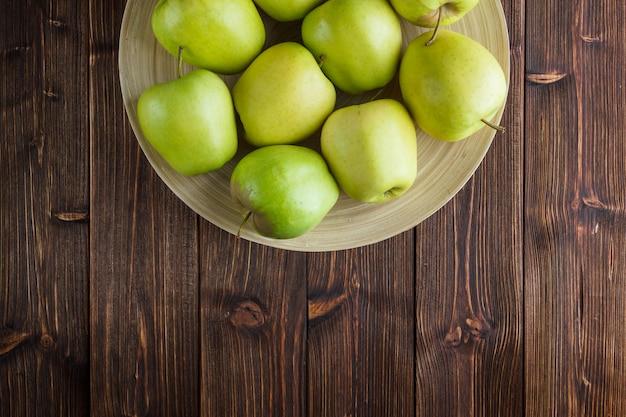 Zieleni jabłka w talerzu na drewnianym tle. widok z góry. miejsce na tekst