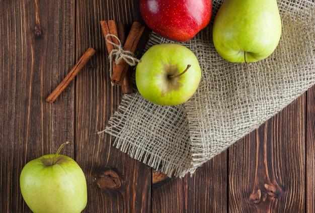 Zieleni jabłka z czerwienią jeden i suchy cynamonowy odgórny widok na drewnianym tle i worze