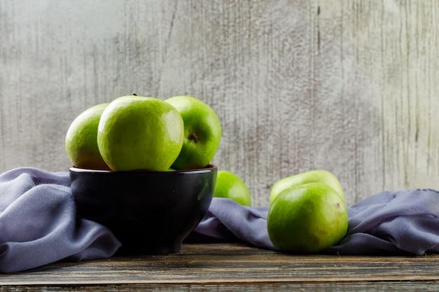 Zieleni jabłka z tkaniną w pucharze na drewnianym i grunge tle